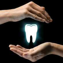 two hands protecting a glowing white tooth